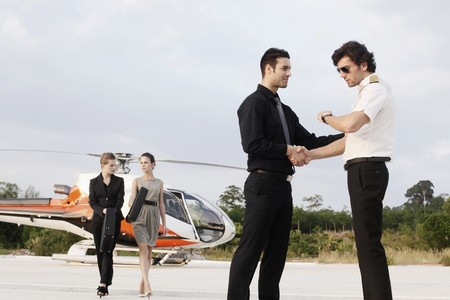 Businessmen shaking hands with pilot while businesswomen are walking away from helicopter photo