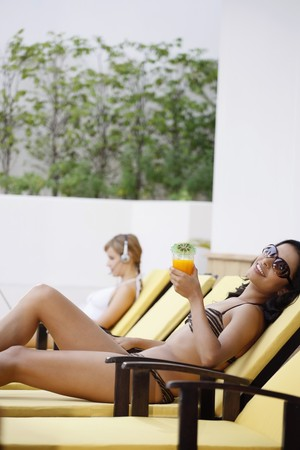 Women relaxing by the pool side photo