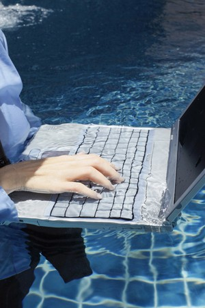 Businesswoman using laptop in swimming pool photo