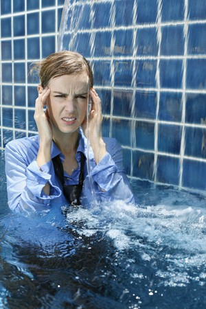 Businesswoman with headache standing in swimming pool photo