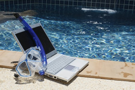 Laptop and diving mask by the pool side Stock Photo - 7595691