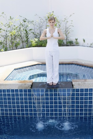 Woman practising yoga by the pool side photo