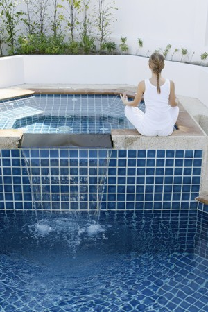 Woman meditating by the pool side Stock Photo - 7595735