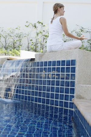 Woman meditating by the pool side Stock Photo - 7595692