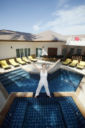Woman standing by the pool side with her hands up photo