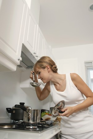 Woman tasting soup in kitchen photo