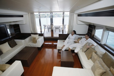 Couple watching television in yacht living room photo