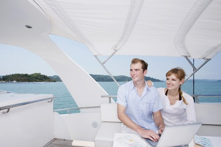 Couple using laptop on yacht with books on the table, looking away photo