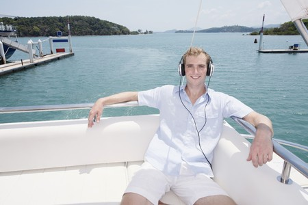 Man listening to headphones on yacht photo