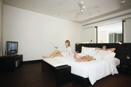 australian ethnicity: Couple relaxing while watching tv in resort bedroom Stock Photo