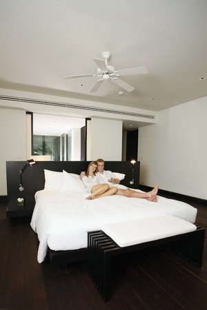 Couple relaxing while watching tv in resort bedroom Stock Photo - 7594672