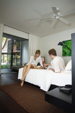 Couple playing chess in resort bedroom Stock Photo - 7595148