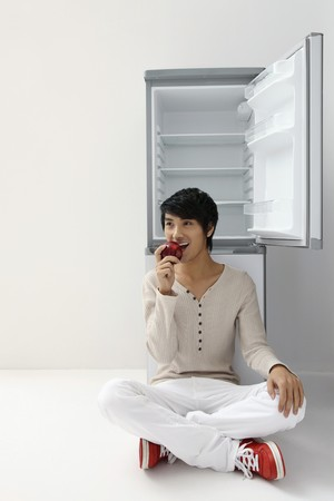 Man sitting in front of refrigerator eating apple photo