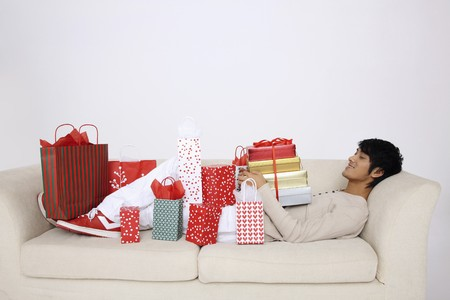 Man lying on the couch with presents on him photo
