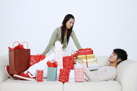 Man lying on the couch with presents, woman looking at him Stock Photo - 7643993