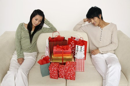 Man and woman sitting on the couch looking at presents photo