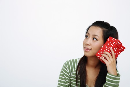 Woman holding a gift box while looking away photo