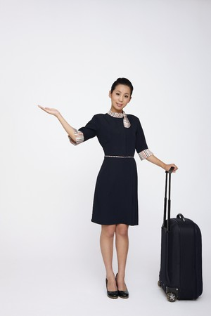 Female flight attendant with luggage, arm outstretched photo
