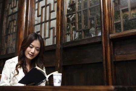mujer leyendo libro: Libro de lectura de mujer en restaurante