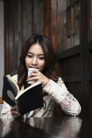 Woman drinking tea while reading book in restaurant photo