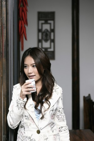 Woman holding a cup of tea while looking out of the window photo