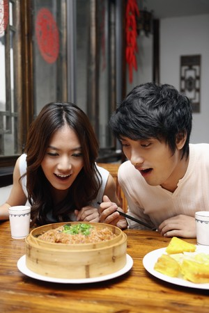 Man and woman looking at food on the table with their mouths wide opened photo