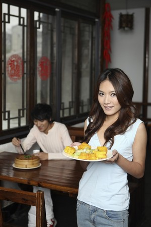 Woman holding a plate of food, man eating in the background photo
