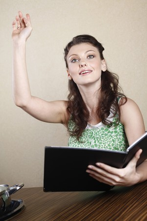 Woman raising hand, calling the waiter photo