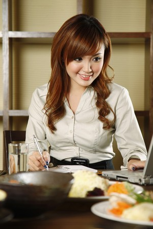 Businesswoman using laptop over lunch at a restaurant Stock Photo - 7643983