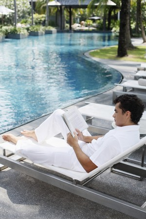Man sitting on lounge chair reading book Stock Photo