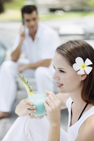 Woman drinking cocktail, man talking on the phone in the background photo