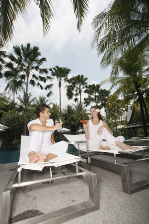 Man and woman on lounge chairs with their drinks photo