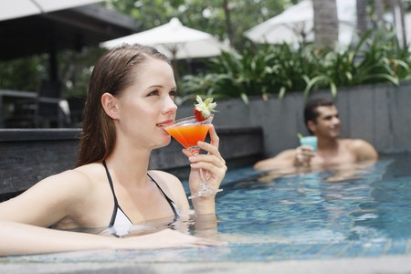 Man and woman drinking while relaxing in the pool photo