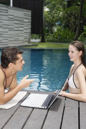 Woman in pool talking to man photo