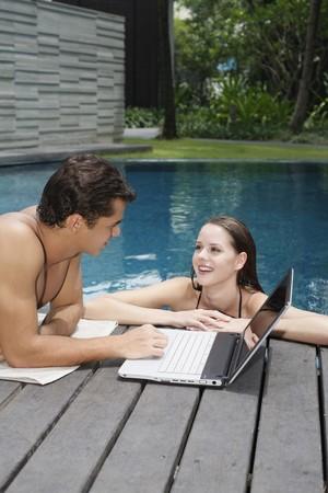 Woman in pool talking to man Stock Photo - 7644059