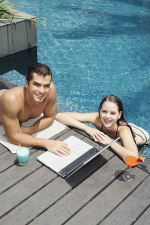 Man using laptop by the pool side, woman in the pool Stock Photo