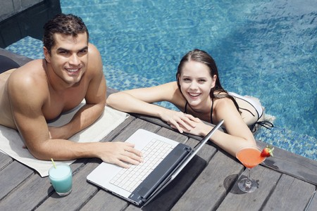 Man using laptop by the pool side, woman in the pool photo