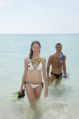 snorkelling: Man and woman with snorkeling gear on beach