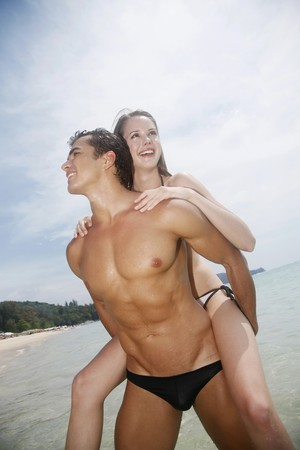 ni�o sin camisa: Hombre a mujer dando un chanchito vuelta cabalgar en playa