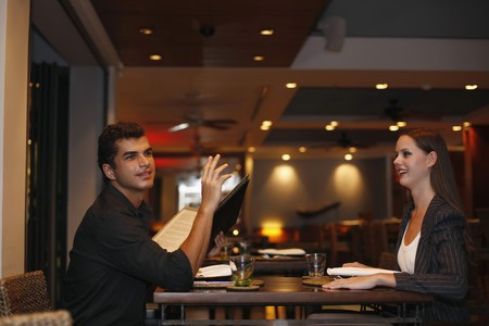 Man holding menu and raising his hand, woman watching man photo