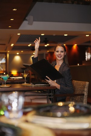 Woman holding menu and raising her hand photo
