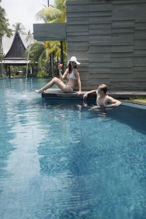 Man in pool talking to woman Stock Photo - 7644299