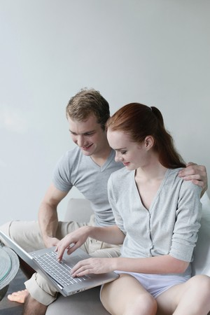 Man and woman using laptop together photo