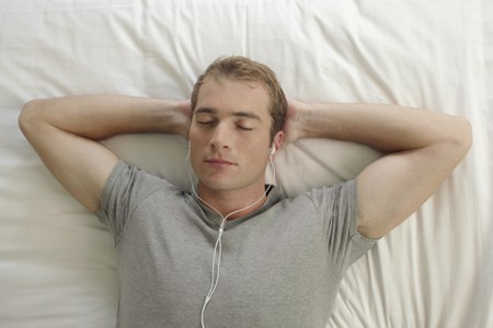 australian ethnicity: Man listening to music in bed, hands behind head Stock Photo