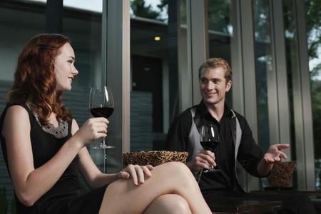 jovenes tomando alcohol: Hombre y mujer, celebraci�n de vasos de vino tinto durante la conversaci�n