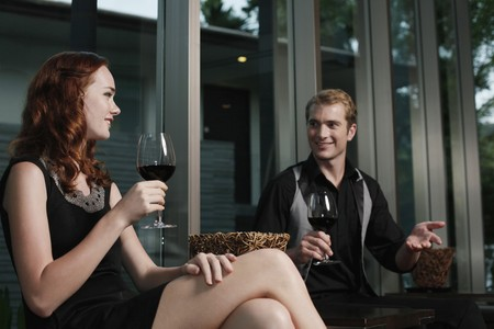 luxury restaurant: Man and woman holding glasses of red wine while chatting
