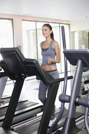 Woman running on treadmill photo
