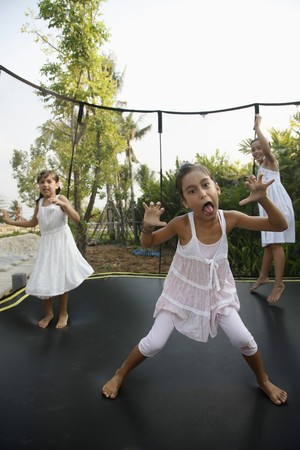 Girls jumping on a trampoline photo