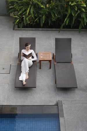 mujer leyendo libro: Mujer leyendo el libro por el lado de la piscina