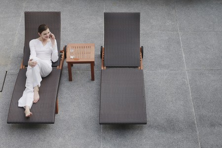 Woman talking on the phone while relaxing on lounge chair Stock Photo - 7644300